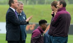 Britain's Prime Minister,  David Cameron, left, chats with England football manager Roy Hodgson, 2nd left, and players, Daniel Sturridge, centre, Steven Gerrard, 2nd right, and Frank Lampard during his visit to England's football training headquarters, St Georges Park, in Burton-Upon-Trent, central England, Thursday, May 29, 2014. (AP Photo/Andrew Yates, Pool)