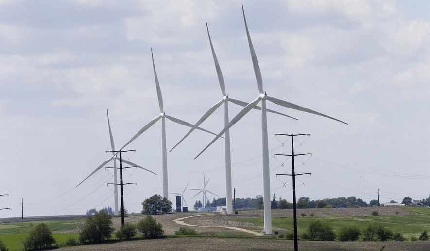 Wind turbines stand in a field, Monday, June 2, 2014, in Adair, Iowa. Iowa utility officials say the Obama administration's ambitious plan to cut carbon dioxide emissions from power plants is likely to increase costs. Iowa utilities invested heavily in wind power over the past decade and improved the efficiency of existing power plants. (AP Photo/Charlie Neibergall)