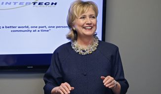 Hillary Clinton smiles at the start of a meeting with community leaders following a tour at Intertech Plastics in Denver, Monday June 2, 2014. The former secretary of state and possible presidential candidate stopped by the Denver plastics manufacturer on Monday to learn more about its training and mentoring of young workers, something she's been focusing on at the Clinton Foundation. (AP Photo/Brennan Linsley)