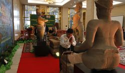 A Cambodian man prays at the three pieces of the 10th century Cambodian sandstone statues displayed after returning from the United States during a handover ceremony at the Council of Ministers in Phnom Penh, Cambodia, Tuesday, June 3, 2014. Cambodia has welcomed back three statues that had been in Western art collections after having been looted from a 1,000-year-old temple during war. (AP Photo/Heng Sinith)