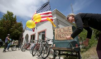 Sondra Van Ert, co-owner of Baldy Sports in Hailey, Idaho, Sgt. Bowe Bergdahl's hometown, ties balloons to a bike trailer in front of her store to celebrate the news of his release. (Associated Press photographs)