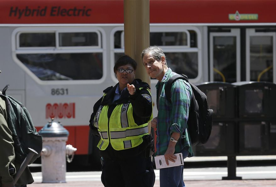 A San Francisco Municipal Transportation Agency fare inspector, left, speaks with a man at the Powell Street cable car turnaround in San Francisco, Tuesday, June 3, 2014. The city's famed cable cars were halted for a second straight day, and the rest of the transit system experienced delays after drivers called in sick again on Tuesday, days after overwhelmingly rejecting a new labor contract, officials said. (AP Photo/Jeff Chiu)