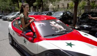 A Syrian woman rides in a car painted in the colors of the Syrian flag with President Bashar Assad's portrait in Damascus, Syria, Tuesday, June 3, 2014. Polls opened in government-held areas in Syria amid very tight security Tuesday for the country's presidential election, a vote that President Bashar Assad is widely expected to win. (AP Photo/Dusan Vranic)