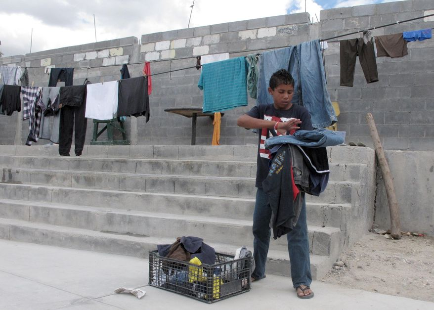 Brian Duran, 14, of Comayagua, Honduras collects his line-dried laundry at the Senda de Vida migrant shelter in Reynosa, Mexico,  June 3, 2014. Duran traveled alone to the U.S.-Mexico border and hopes to soon become one of the more than 47,000 unaccompanied children to enter the United States since Oct. 1, 2013. (AP Photo/Chris Sherman)