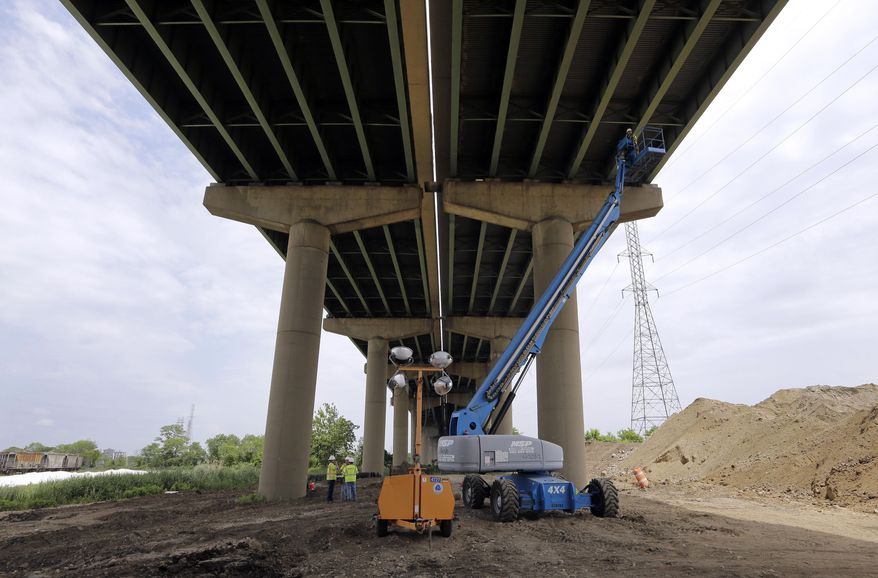 A worker inspects the underside of the Interstate 495 bridge over the Christina River near Wilmington, Del., Tuesday, June 3, 2014, after it was closed due to the discovery of four tilting support columns. The closure created heavier-than-normal traffic conditions for motorists on Interstate 95, a major East Coast artery. The bridge normally carries about 90,000 vehicles a day. (AP Photo/Patrick Semansky)