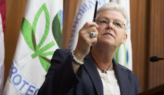 ** FILE ** Environmental Protection Agency (EPA) Administrator Gina McCarthy holds up a pen before signing new emission guidelines during an announcement of a plan to cut carbon dioxide emissions from power plants by 30 percent by 2030, Monday, June 2, 2014, at EPA headquarters in Washington.  (AP Photo/ Evan Vucci)