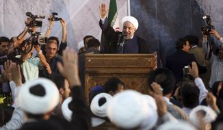 Iranian President Hassan Rouhani waves as he arrives to deliver a speech during a ceremony marking the 25th death anniversary of Ayatollah Khomeini, the founder of the Islamic Republic, at his shrine just outside Tehran, Iran, Tuesday, June 3, 2014. Iran's moderate president said Tuesday that his administration will defend the Islamic Republic's nuclear rights and work to end international sanctions that have devastated its economy. (AP Photo/Vahid Salemi)