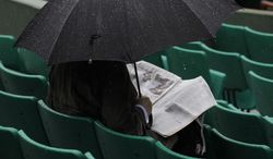 A lone spectator reads under an umbrella in the stands of  the Roland Garros stadium, in Paris, France, Wednesday, June 4, 2014. Rain delayed the start of the quarterfinal matches of the French Open tennis tournament. (AP Photo/Darko Vojinovic)