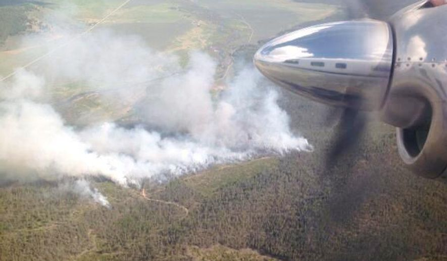 This photo provided by the U.S. Forest Service, shows smoke from a 60-acre wildfire burning in a popular tourist area about 10 miles south of Stanley in central Idaho. The mountainous area is heavily traveled by tourists starting this time of year, U.S. Forest Service spokeswoman Julie Thomas said. It's in the Sawtooth National Recreation Area, which draws hikers, rafters, rock climbers, anglers, mountain bikers and other outdoor enthusiasts.  (AP Photo/U.S. Forest Service)