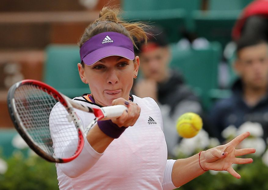 Romania's Simona Halep returns the ball to Russia's Svetlana Kuznetsova during their quarterfinal match of  the French Open tennis tournament at the Roland Garros stadium, in Paris, France, Wednesday, June 4, 2014. (AP Photo/Michel Spingler)