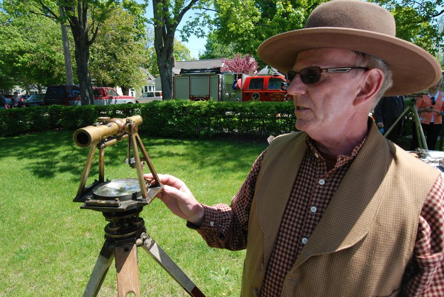 In this Saturday, May 31, 2014 photo, Larry O'Donnell of the Pentwater Historical Society wears period costume to show surveying tools such as this 1800s transit  during the dedication festivities for the new museum the society opened in Pentwater, Mich. (AP Photo/Ludington Daily News, Steve Begnoche) MANDATORY CREDIT