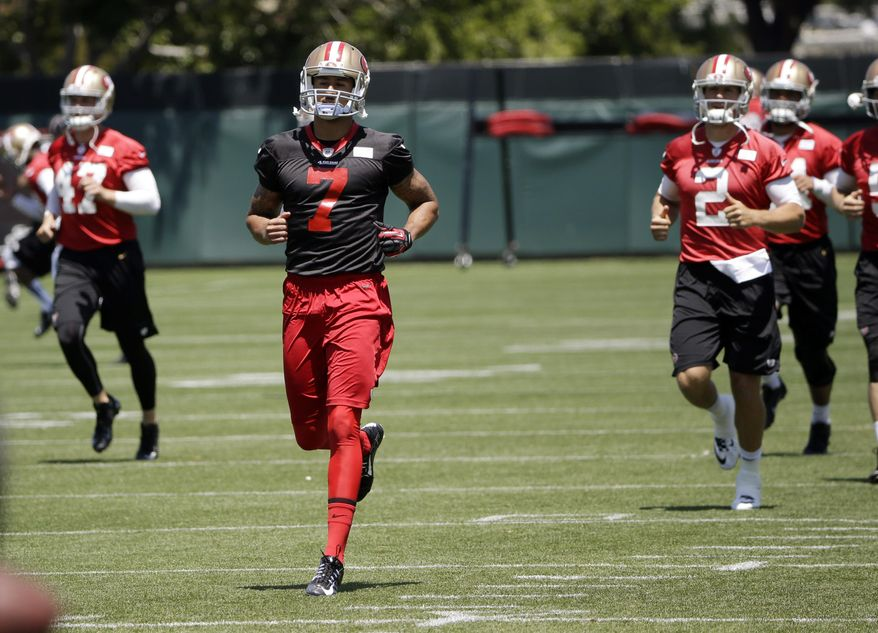 San Francisco 49ers quarterback Colin Kaepernick (7) runs with teammates during an NFL football organized team activity, Tuesday, June 3, 2014, in Santa Clara, Calif. (AP Photo/Marcio Jose Sanchez)