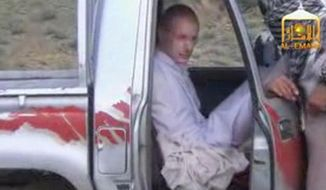 In this image taken from video obtained from Voice Of Jihad Website, which has been authenticated based on its contents and other AP reporting, Sgt. Bowe Bergdahl sits in a vehicle guarded by the Taliban in eastern Afghanistan. The Taliban have released a video showing the handover of Bergdahl to U.S. forces in eastern Afghanistan. The video, emailed to media on Wednesday, shows Bergdahl in traditional Afghan clothing sitting in a pickup truck parked on a hillside. More than a dozen Taliban fighters with machine guns stand around the truck and on the hillside. (AP Photo/Voice Of Jihad Website via AP video)