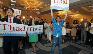 Supporters for U.S. Sen. Thad Cochran, R-Miss., cheer and wave signs as they wait for comments from his campaign staff, Tuesday, June 3, 2014 in Jackson, Miss. Tea party favorite Chris McDaniel and six-term Cochran dueled inconclusively Tuesday night in Mississippi's Republican primary election. (AP Photo/Rogelio V. Solis)
