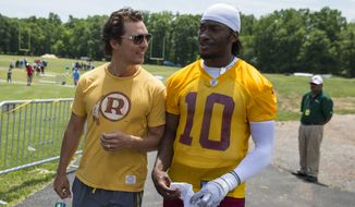 Academy Award winning actor Matthew McConaughey, left, walks with Washington Redskins quarterback Robert Griffin III after an NFL football practice at Redskins Park, on Wednesday, June 4, 2014, in Ashburn, Va. (AP Photo/ Evan Vucci)