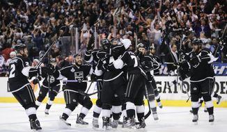 Members of the Los Angeles Kings celebrate Justin Williams's goal in overtime of Game 1 in the NHL Stanley Cup Final hockey series against the New York Rangers on Wednesday, June 4, 2014, in Los Angeles.(AP Photo/Jae C. Hong)