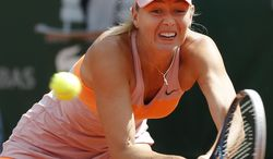 Russia's Maria Sharapova returns the ball during the semifinal match of the French Open tennis tournament against Canada's Eugenie Bouchard at the Roland Garros stadium, in Paris, France, Thursday, June 5, 2014. (AP Photo/Michel Euler)