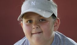 Isabella Newcomer waits for her Little League softball game to begin in Williamsport, Pa. , May 28, 2014. She is a great granddaughter of Dick Hauser who played on one of the original Little League teams in 1939, making her a fourth generation Little Leaguer. (AP Photo/Ralph Wilson)