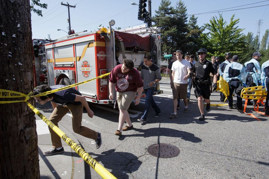 """Seattle Pacific University students are lead out of the crime scene area after a shooting occurred on the university's campus Thursday, June 5, 2014, in Seattle. The university posted online Thursday that """"the campus is in lockdown due to a shooting near Otto Miller Hall."""" (AP Photo/The Seattle Times, Dean Rutz)  SEATTLE OUT; USA TODAY OUT; MAGS OUT; TELEVISION OUT; NO SALES; MANDATORY CREDIT TO BOTH THE SEATTLE TIMES AND THE PHOTOGRAPHER"""