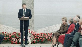Photo shows general view of the ceremony at Pointe Du Hoc, France, on Wednesday, June 6, 1984 as President Ronald Reagan delivers his speech shortly after his arrival in Normandy.   Sitting are right is Mrs. Nancy Reagan with veterans of the 2nd Ranger Battalion that conquered the cliffs. Left, the memorial monument remembering the invasion 40 years ago. (AP Photo/Ron Edmonds)