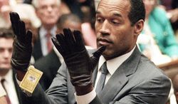 FOR USE SUNDAY, JUNE 8, 2014, AND THEREAFTER- FILE - June 21, 1995 file photo, O.J. Simpson holds up his hands before the jury after putting on a new pair of gloves similar to the infamous bloody gloves during his double-murder trial in Los Angeles. Associated Press writer Linda Deutsch is seen in the background at right; writer Dominick Dunne is in the background at left rear. (AP Photo/Vince Bucci, Pool, File)