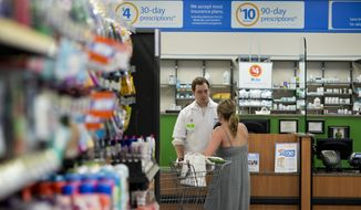 Jay Hungerford, pharmacy intern, speaks with a customer at Wal-Mart Neighborhood Market in Bentonville, Ark., Thursday June 5, 2014. (AP Photo/Sarah Bentham) ** FILE **