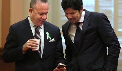 ** FILE ** State Senate President Pro Tem Darrell Steinberg, D-Sacramento, left, and Sen. Kevin de Leon, D-Los Angeles look over Steinberg's smart phone as lawmakers debated a measure requiring electronics manufacturers to install a shut-off function on all smartphones manufactured and sold after July 2015,  at the Capitol  in Sacramento, Calif., Thursday May 8, 2014. (AP Photo/Rich Pedroncelli)