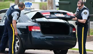 Royal Canadian Mounted Police check the trunk of a taxi at a roadblock in Moncton, New Brunswick on Thursday, June 5, 2014. A RCMP manhunt for a gunman suspected of killing three Mounties and wounding two others passed the 12-hour mark Thursday in Moncton as a large section of the New Brunswick city was under a virtual siege. (AP Photo/The Canadian Press, Marc Grandmaison)