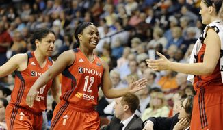 Washington Mystics' Ivory Latta, center, and teammate Kara Lawson, left, are greeted on bench by Stefanie Dolson during the second half of a WNBA basketball game against the Connecticut Sun, Thursday, June 5, 2014, in Uncasville, Conn. The Mystics defeated the Sun 74-66. (AP Photo/Jessica Hill) **FILE**