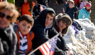 A young spectator, second from right, covers his ears as members of the 1st Virginia Regiment march past him in the annual Old Town Alexandria President's Day Parade, Alexandria, Va., Monday, February 17, 2014. (Andrew Harnik/The Washington Times)