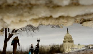 People walk past melting ice and water puddles near the U.S. Capitol Building on the National Mall, Washington, D.C., Tuesday, March 18, 2014. (Andrew Harnik/The Washington Times)