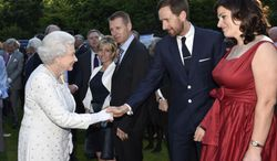 Britain's Queen Elizabeth II, left, shakes hands with Tour de France winner Bradley Wiggins, second right, as she attends a garden party hosted by Britain's Ambassador to France Peter Ricketts, ahead of marking the 70th anniversary of the D-Day landings during World War II, in Paris, Thursday, June 5, 2014. (AP Photo/Owen Humphreys, PA Wire)    UNITED KINGDOM OUT    -   NO SALES   -   NO ARCHIVES