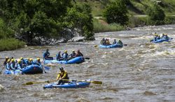 In this June 5, 2014 photo, rafters with Mountain Whitewater Descents spend the afternoon enjoying the Poudre River in Fort Collins, Colo. Authorities say they will not restrict access to the Poudre (POO-der) River near Fort Collins after the swollen waterway claimed its third victim in less than two weeks. (AP Photo/The Coloradoan, Erin Hull)