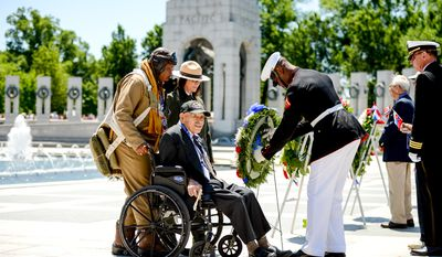 Park Service Historian John McCaskill, left, National Mall Deputy Superintendent Karen Cucurullo, second from left,  stand with World War II veteran Air Force Buck Sgt. Henry Mendoza, 94, of Ontario, Calif., center, during a wreath laying ceremony for the 70th anniversary commemoration ceremony of D-Day at the National World War II Memorial on the National Mall, Washington, D.C., Friday, June 6, 2014. (Andrew Harnik/The Washington Times)