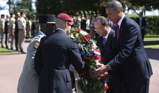 U.S. President Barack Obama, right and French President Francois Hollande place a wreath, at the Normandy American Cemetery, at Omaha Beach as they participate in the 70th anniversary of D-Day in Colleville sur Mer in Normandy, France, Friday, June 6, 2014. (AP Photo/Charles Dharapak)