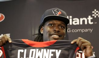 Houston Texans No. 1 overall draft pick Jadeveon Clowney, a defensive end from South Carolina, holds up his new jersey during an introductory NFL football news conference Friday, May 9, 2014, in Houston. (AP Photo/Pat Sullivan)
