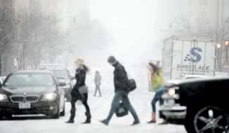Pedestrians make their way through Chinatown as snow accumulates in the Washington region, Washington, D.C., Tuesday, January 21, 2014. (Andrew Harnik/The Washington Times) ** FILE **