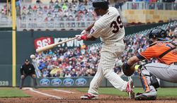 Minnesota Twins' Danny Santana drives in two runs with a single in the second inning off Houston Astros' pitcher Scott Feldman in a baseball game, Saturday, June 7, 2014, in Minneapolis. (AP Photo/Jim Mone)