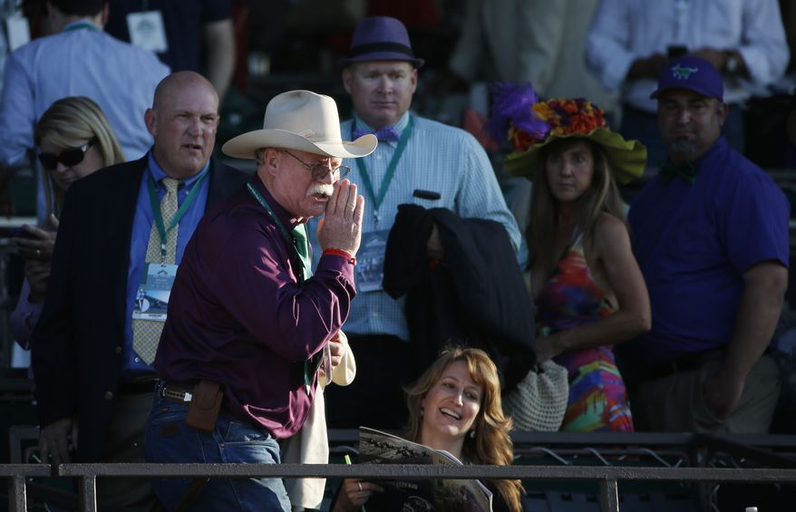 California Chrome co-owner Steve Coburn calls from the grandstand at Belmont Park after his horse finished fourth in the Belmont Stakes horse race, Saturday, June 7, 2014, in Elmont, N.Y. (AP Photo/Kathy Willens)