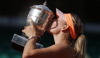 Russia's Maria Sharapova kisses the trophy  after winning the final of the French Open tennis tournament against Romania's Simona Halep at the Roland Garros stadium, in Paris, France, Saturday, June 7, 2014. Sharapova won in three sets 6-4, 6-7, 6-4. (AP Photo/Michel Euler)