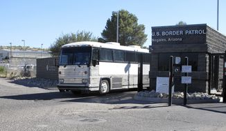 A bus leaves the entrance of the U. S. Border Patrol facility on Saturday, June 7, 2014 in Nogales, Ariz. Arizona officials said they are rushing federal supplies to this makeshift holding center in the southern part of the state that's housing hundreds of migrant children and is running low on the basics. (AP Photo/Brian Skoloff)