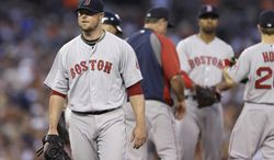 Boston Red Sox starting pitcher Jon Lester heads to the dugout after being removed during the fifth inning of a baseball game against the Detroit Tigers in Detroit, Saturday, June 7, 2014. (AP Photo/Carlos Osorio)