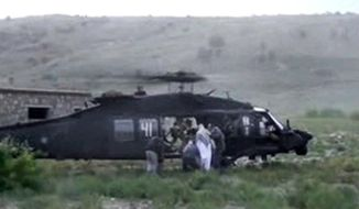 FILE - This image taken from video obtained from Voice Of Jihad Website, authenticated based on its contents and other AP reporting, shows men in civilian clothing leading Sgt. Bowe Bergdahl, in white, towards a helicopter in eastern Afghanistan.  Bergdahl was freed on May 31, 2014, in exchange for five Afghan detainees held in the U.S. prison at Guantanamo Bay, Cuba. Two American values, never leave a man behind and never negotiate with terrorists, collided in the Bergdahl calamity. Each ethos runs deep in the American conscience, yet has been violated through history and notably in the age of terrorism, where traditional standards of warfare, spying and negotiating are run through a hall of mirrors. (AP Photo/Voice Of Jihad Website via AP video)