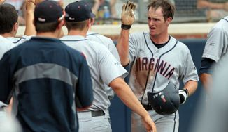 Virginia catcher Robbie Coman (8), right, celebrates scoring with teammates in the third inning of an NCAA college baseball tournament super regional game against Maryland in Charlottesville, Va., Sunday, June 8, 2014.  (AP Photo/Andrew Shurtleff)