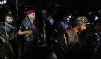 Pakistani commandos get ready to enter Karachi airport terminal following attacks by unknown gunmen on Sunday night, June 8, 2014, in Pakistan. Gunmen stormed an airport terminal used for VIPs and cargo in Pakistan's largest city on Sunday night, killing and wounding scores of people, officials said. (AP Photo/Shakil Adil)