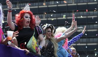 **FILE** Drag queens wave to spectators during the annual Pride Day Parade, Sunday June 8, 2014, in Philadelphia. (AP Photo/ Joseph Kaczmarek)