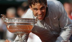 Spain's Rafael Nadal bites the trophy after winning the final of the French Open tennis tournament against Serbia's Novak Djokovic at the Roland Garros stadium, in Paris, France, Sunday, June 8, 2014. Nadal won in four sets 3-6, 7-5, 6-2, 6-4. (AP Photo/Michel Euler)