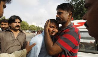 People comfort a family member of a security officer killed in late Sunday's attack at the Jinnah International Airport in Karachi, Pakistan, Monday, June 9, 2014. The Pakistani Taliban on Monday claimed responsibility for a brazen five-hour assault on the country's busiest airport that saw gunmen disguised as police guards storm the international terminal in Karachi, set off explosions and killing over a dozen of people. (AP Photo/Fareed Khan)