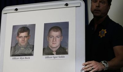 Pictures of Las Vegas Metropolitan Police Officers Alyn Beck, left, and Igor Soldo are seen a a news conference Sunday, June 8, 2014 in Las Vegas. The two officers were killed in an ambush while eating lunch. (AP Photo/John Locher)