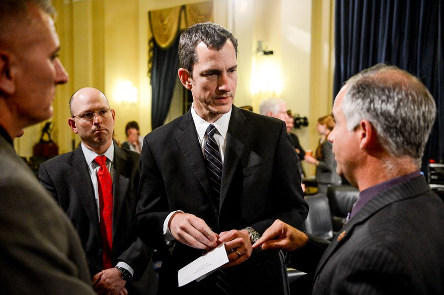 Rep. Tim Huelskamp (R-Kan.), right, speaks to Veteran Affairs Undersecretary for Health for Administrative Operations Assistant Deputy Philip Matkovsky, center, during a break in his testimony in front of a House Veterans' Affairs Committee hearing on Capitol Hill, Washington, D.C., Monday, June 9, 2014. (Andrew Harnik/The Washington Times)